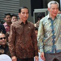 Presiden RI, Joko Widodo bersama PM Singapura Lee Hsien Loong menyaksikan manuver F16 Angkatan Udara Singapura dan F16 TNI-AU dalam peringatan 50 tahun hubungan bilateral Indonesia dan Singapura di Singapura, Kamis (7/9). (AFP Photo/Roslan Rahman)