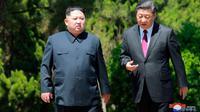 Pemimpin Korea Utara Kim Jong-un dan Presiden China Xi Jinping berbincang sambil berjalan di sela pertemuan di Dalian, Selasa (8/5). Ini adalah kunjungan kedua Kim ke China dalam dua bulan terakhir. (Korean Central News Agency/Korea News Service via AP)