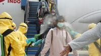 Petugas menyemprotkan cairan disinfektan ke WNI yang dievakuasi dari Wuhan, China saat tiba di bandara internasional Hang Nadim, Batam, Minggu (2/2/2020). Sebanyak 245 WNI di Wuhan dievakuasi ke Indonesia terkait merebaknya virus corona di kota tersebut. ((Photo by Handout/Indonesian Embassy/AFP)