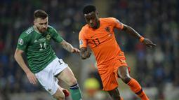 Gelandang Belanda, Quincy Promes, beradu cepat dengan gelandang Irlandia Utara, Stuart Dallas, pada laga Kualifikasi Piala Eropa 2020 di Windsor Park, Belfast, Sabtu (16/11). Kedua negara bermain imbang 0-0. (AFP/Mark Marlow)