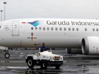 Teknisi mengendarai mobil melewati pesawat Boeing 737 Max 8 Garuda Indonesia yang terparkir di Bandara Soekarno Hatta, Tangerang, Rabu (13/3). Pemerintah menetapkan pelarangan permanen untuk pesawat Boeing 737 Max 8 terbang. (REUTERS/Willy Kurniawan)