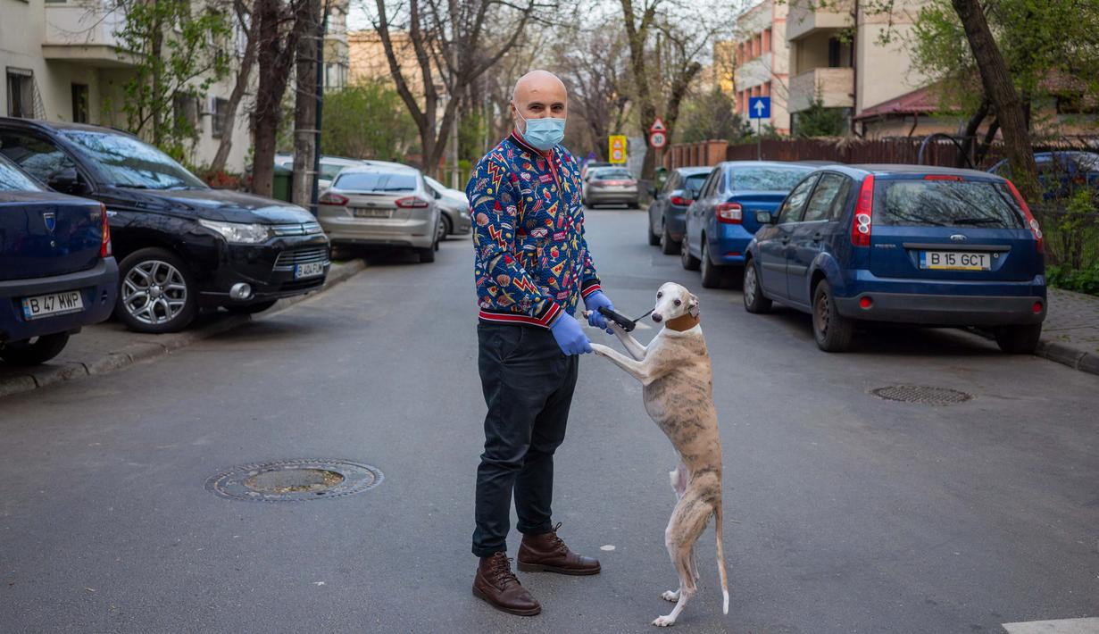 George Popa (51) berpose dengan anjing Ziggy (7) saat perjalanan di Bucharest (28/3/2020). Undang-undang militer, yang disahkan pemerintah Rumania untuk mengurangi penyebaran virus corona, menyatakan berjalan bersama anjing adalah salah satu  kegiatan yang masih diizinkan. (AFP/Andrei Pungovschi)