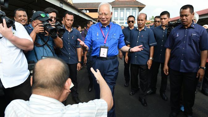 Perdana Menteri Malaysia, Najib Razak menyapa seorang pendukung di tempat pemungutan suara selama pemilihan umum di Pekan, Rabu (9/5). Pemilu ini pertarungan antara PM Najib yang sudah berkuasa sejak 2009, melawan Mahathir Mohamad. (MOHD RASFAN / AFP)#source%3Dgooglier%2Ecom#https%3A%2F%2Fgooglier%2Ecom%2Fpage%2F%2F10000