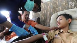 Seorang anak diambil sampel darah di RT1-2/1 Kelurahan Cinere, Depok, Rabu (28/6/2019). Dinas Kesehatan Depok dan Puskesmas Cinere melakukan investigasi sumber penyakit dan sampel darah warga di kawasan ini terkait sudah lebih dari sepekan 12 warga terjangkit hepatitis A. (merdeka.com/Arie Basuki)