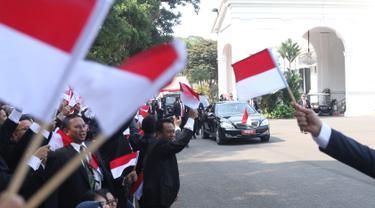 Pegawai Istana mengibarkan bendera merah putih saat rombongan mobil Presiden terpilih Joko Widodo (Jokowi)  melintas menuju gedung DPR di Istana Kepresidenan, Jakarta, Minggu (20/10/2019). Jokowi-Ma'ruf Amin kembali dilantik sebagai Presiden-Wapres RI periode 2019-2024. (Liputan6.com/Angga Yuniar)