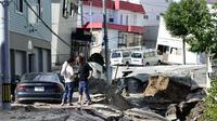 Sejumlah warga melihat kondisi jalan yang mengalami kerusakan parah akibat Gempa magnitudo 6,7 di Sapporo, Hokkaido, Jepang, Kamis (6/9). (Hiroki Yamauchi/Kyodo News via AP)