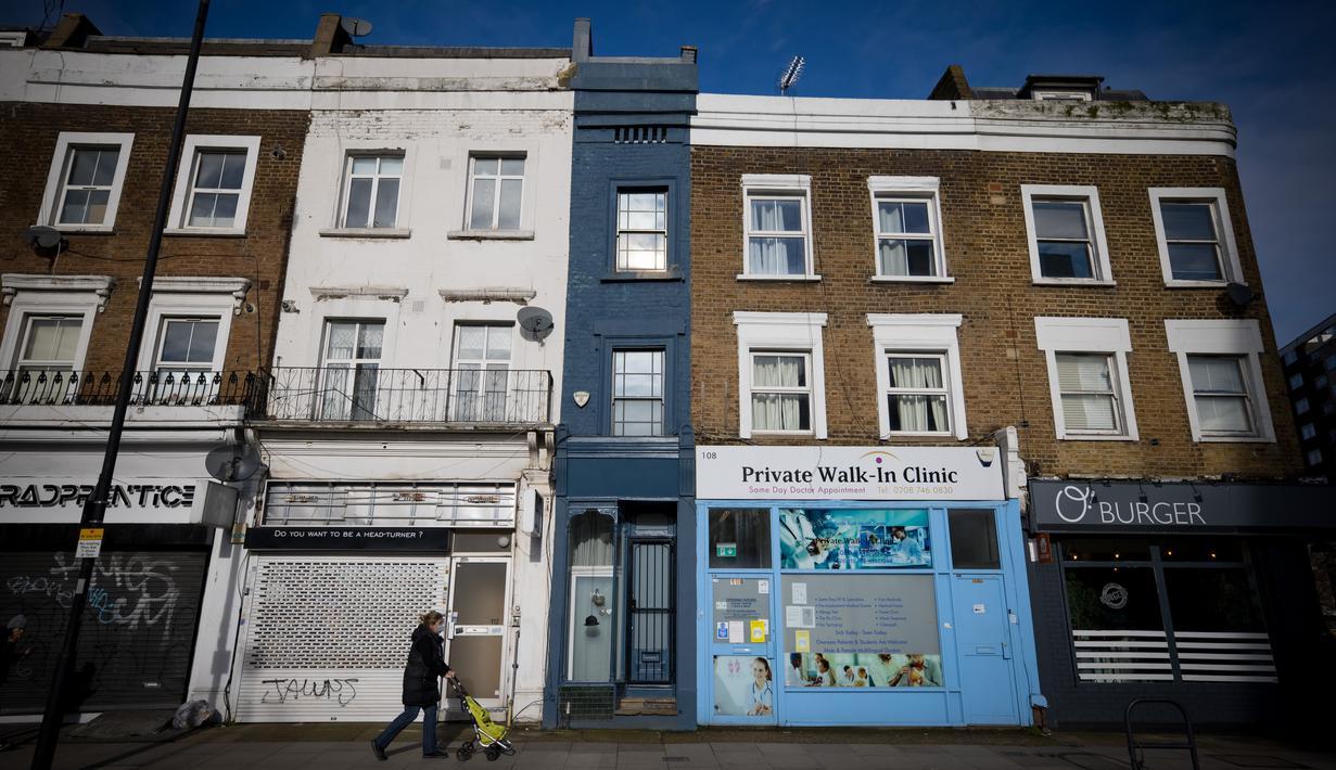 """Seorang pejalan kaki melewati bagian depan bangunan yang dijuluki """"Rumah Tersempit di London"""" (cat biru) di London barat pada 5 Februari 2021. Terjepit di antara praktek dokter dan salon penata rambut, rumah mungil tersebut hanya memiliki lebar 1,6 meter dan panjang 7,31 meter. (Tolga Akmen/AFP)"""