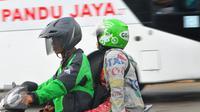 Pengendara ojek online bersama penumpang melintas di kawasan Terminal Kalideres, Jakarta, Selasa (22/3). Dengan adanya aksi demo angkutan umum di ruas Jakarta penumpang terlantar di sejumlah terminal. (Liputan6.com/Faisal R Syam)