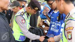 Polisi memeriksa tas yang dibawa oleh para Bobotoh saat memasuki kawasan SUGBK, Jakarta, Minggu (18/10/2015). Kedatangan Bobotoh untuk mendukung Persib Bandung melawan Sriwijaya FC di Final Piala Presiden 2015 (Liputan6.com/Herman Zakharia)