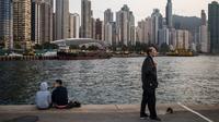 Orang-orang bersantai di dermaga umum di sebelah Pelabuhan Victoria di Hong Kong (3/3). Pemandangan yang spektakuler membuat pelabuhan ini menjadi daya tarik wisata utama Hong Kong. (AFP Photo/Dale De La Rey)
