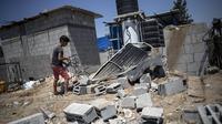 Seorang anak di Palestina melihat rumahnya yang hancur usai bentrokan Hamas dan Israel. Dok: AP Photo