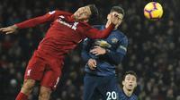 Penyerang Liverpool, Roberto Firmino berebut bola dengan pemain Manchester United, Diogo Dalot pada lanjutan pekan ke-17 Premier League di Stadion Anfield, Minggu (16/12). The Reds mengalahkan rival abadi, Manchester United dengan skor 3-1 (AP/Rui Vieira)