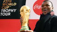 Mantan bek Prancis, Marcel Desailly berpose dengan trofi Piala Dunia dengan latar menara Eiffel selama FIFA World Cup Trophy Tour di Paris (20/3). Piala Dunia 2018 diselenggarakan 14 Juni dan 15 Juli 2018 di Rusia. (AFP Photo/Franck Fife)