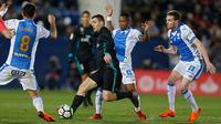 Pemain Real Madrid, Mateo Kovacic mengendalikan bola dengan kawalan pemain Leganes pada partai tunda pekan ke-16 La Liga Spanyol di Estadio Municipal de Butarque, Rabu (21/2). Madrid menang 3-1 atas Leganes meski sempat ketinggalan. (AP/Francisco Seco)