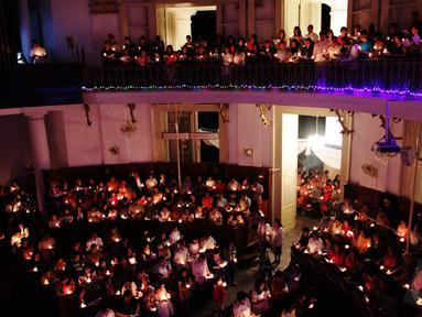 Umat Kristiani menyalakan lilin saat mengikuti Misa Natal di Gereja Immanuel Jakarta, Rabu (24/12/2014). (Liputan6.com/Faizal Fanani)
