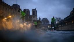 Para peserta Nautic Paddle Race atau lomba dayung sambil berdiri melintas dekat Katedral Notre-Dame di Paris, Minggu (8/12/2019). Sekitar 1000 pesaing ikut serta dalam lomba sejauh 11 kilometer menyeberangi sungai Seine dengan pemandangan kota Paris. (Photo by Olivier MORIN / AFP)