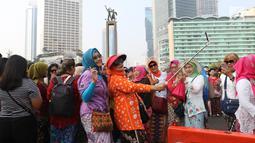 Emak-emak dari masyarakat pencinta kebaya dan sarung Indonesia berselfie saat mengikuti parade di Bundaran HI, Jakarta, Minggu (28/7/2019). Parade tersebut bertujuan untuk mengajak masyarakat agar mencintai busana tradisional khas Indonesia. (Liputan6.com/Angga Yuniar)