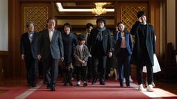 Sutradara Bong Joon Ho  dan Presiden Korea Selatan Moon Jae-in berjalan untuk makan siang di Blue House, Seoul, Kamis (20/2/2020). Presiden Moon mengundang Sutradara Bong Joon Ho dan seluruh tim untuk merayakan kemenangan Parasite yang membawa pulang empat Piala Oscar 2020. (KIM HONG-JI/AFP)