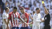 Wasit Xavier Estrada memberikan kartu kuning kepada gelandang Real Madrid, Toni Kross, saat melawan Atletico Madrid pada laga La Liga Spanyol di Stadion Santiago Bernabeu, Madrid, Minggu (8/4/2018). Kedua klub bermain imbang 1-1. (AFP/Gabriel Bouys)