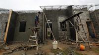 Pekerja menyelesaikan pembangunan rumah di kawasan perumahan subsidi, Rajeg, Tangerang, Banten, Kamis (11/2/2021). Bank BTN dan Kementerian PUPR memberikan program penyaluran skema Kredit Pemilikan Rumah Bantuan Pembiayaan Perumahan Berbasis Tabungan. (Liputan6.com/Angga Yuniar)