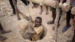 Seorang buruh tambang saat keluar dari lubang tanah usai mencari safir di kawasan pertambangan batu safir di Sakaraha, Madagaskar. Batu Safir pertama kali ditemukan di Madagaskar pada akhir 1990-an. (AFP Photo/Gianluigi Guercia)