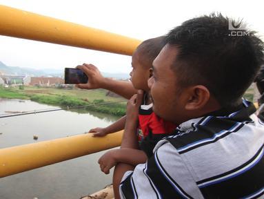 Warga mengabadikan kendaraan pemudik yang melintasi Jembatan Kali Kuto di ruas tol fungsional Batang-Semarang, Gringsing, Jateng, Rabu (13/6). Berfungsinya Jembatan ini akan memperlancar arus mudik dan arus balik Lebaran 2018. (Liputan6.com/Arya Manggala)