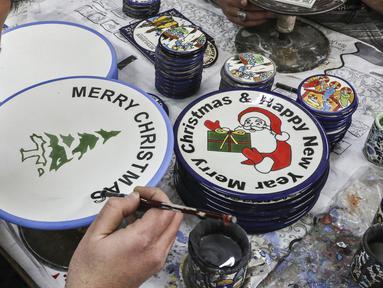 Pekerja Palestina menggambar hiasan bertema Natal di atas piring keramik di sebuah pabrik keramik di kota titik nyala Hebron di Tepi Barat (17/12/2019). (AFP/Hazem Bader)