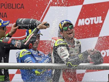 Pebalap LCR Honda, Cal Crutchlow (kanan), merayakan gelar juara pada MotoGP Argentina di Sirkuit Termas de Rio Hondo, Minggu (8/4/2018). Pebalap Inggris itu mencatatkan waktu 40 menit 36.342 detik. (AFP/Juan Mabromata)