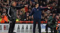 Pelatih Sheffield United Chris Wilder (kiri) dan pelatih Arsenal Unai Emery (kanan) memberi arah dari tepi lapangan saat anak asuh mereka bertanding pada pertandingan Liga Inggris di Bramall Lane, Sheffield, Inggris, Senin (21/10/2019). Sheffield United menang1-0. (Oli SCARFF/AFP)