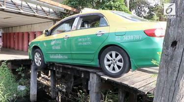 Sebuah taksi tersangkut di jembatan kayu di Thailand. Peristiwa itu terjadi saat sopir akan menjemput penumpang di wilayah  Chachoengsao.