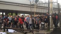 Massa HMI Unibos Makassar merusak pagar kantor Kejati Sulsel saat berunjuk rasa menagih keseriusan Kejati Sulsel menangkap buron kasus korupsi penyewaan lahan negara dan dugaan TPPU di Makassar, Jentang (Liputan6.com/ Eka Hakim)