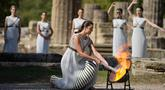 Aktris Yunani Xanthi Georgiou yang berperan sebagai High Priestess menyalakan obor saat menyalakan api Olimpiade di situs Olympia, Yunani, Senin (18/10/2021). Nyala api akan dibawa dengan obor estafet ke Beijing yang menjadi tuan rumah Olimpiade 2022. (AP Photo/Thanassis Stavrakis)