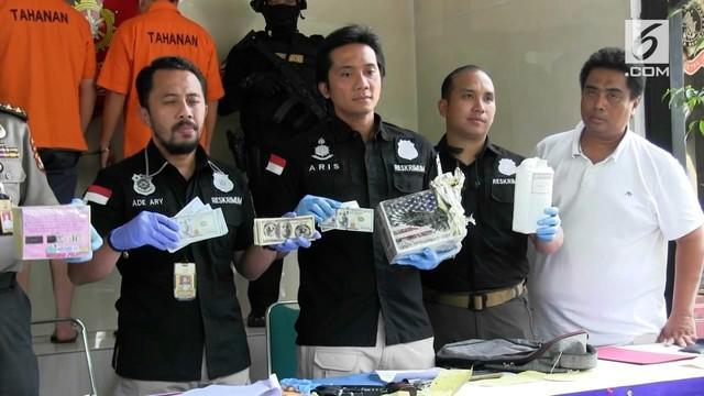 Polisi menangkap dua orang yang menipu dengan modus memberikan modal investasi dengan menggunakan uang dolar palsu.