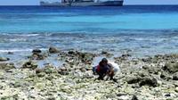 Bocah bermain di Pantai dengan latar belakang KRI Yos Sudarso 353 saat berlabuh di Miangas, Sulut. KRI tersebut memantau keamanan pulau terluar Indonesia yang berbatasan Filipina.(Antara)