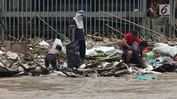 Pemulung bersama sejumlah anak mencari botol-botol plastik yang tersangkut diantara tumpukan sampah di Pintu Air Manggarai, Jakarta, Jumat (26/4). Sampah ini terbawa arus sungai Ciliwung akibat curah hujan yang tinggi di kawasan Bogor dan sekitarnya, Kamis (25/4). (Liputan6.com/Helmi Fithriansyah)