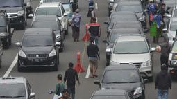 Antrean kendaraan saat hendak keluar tol Jagorawi menuju jalur Puncak di Bogor, Jawa Barat, Sabtu (22/12). Parahnya antrean jelang libur Natal dan Tahun Baru membuat kepolisian setempat memberlakukan sistem buka tutup jalur. (Merdeka.com/Imam Buhori)