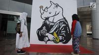 Dua anak kecil melihat-lihat karya dalam pameran seni badak Sumatera di Perpustakaan Nasional Indonesia, Jakarta Pusat, Jumat (19/1). Karya para seniman tersebut akan didonasikan kepada Konsorsium Konservasi Badak Sumatera. (Liputan6.com/Arya Manggala)