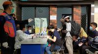 Para penumpang antri menunggu giliran rapid test antigen sebelum jadwal keberangkatan kereta api di Stasiun Malang (Liputan6.com/Zainul Arifin)