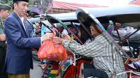 Presiden Joko Widodo atau Jokowi saat membagikan sembako kepada tukang becak di Pasar Harum Manis, Banjarmasin, Kalimantan Selatan. (Liputan6.com/Ahmad Romadoni)