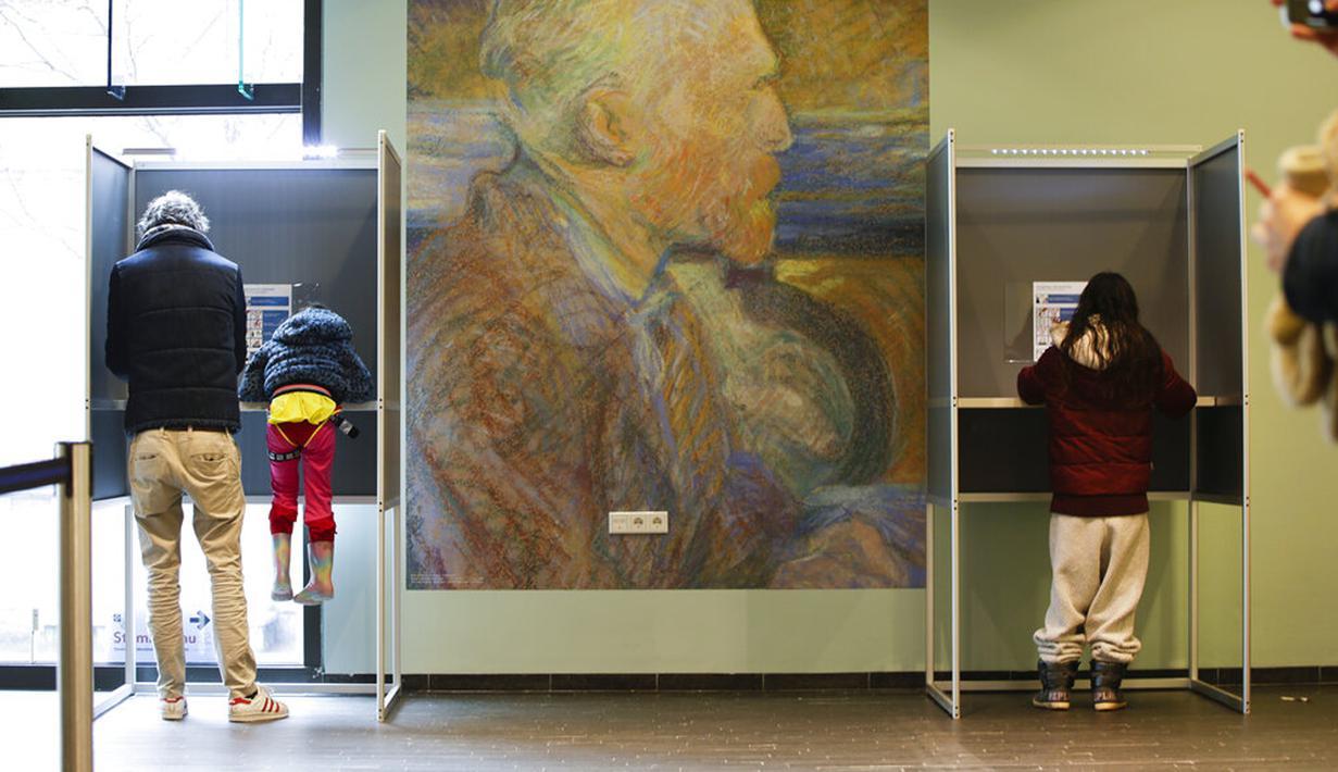 Seorang pria bersama anaknya (kiri) memberikan suara di bilik suara dalam pemilihan umum di Museum Van Gogh, Amsterdam, Belanda, Rabu (17/3/2021). Pemilu digelar selama tiga hari untuk memungkinkan warga memilih dengan aman selama pandemi virus corona COVID-19. (AP Photo/Peter Dejong)