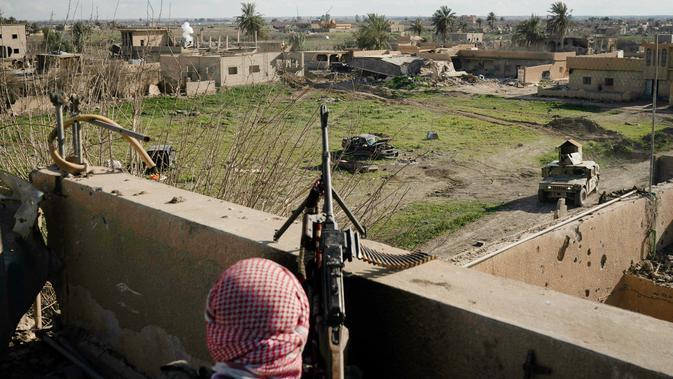 Anggota Syrian Democratic Forces (SDF) mengintai militan ISIS dari sebuah bangunan di kantong terakhir kekhalifahan di Baghouz, Suriah, Senin (18/2). ISIS dilaporkan kian terkepung. (AP Photo/Felipe Dana)