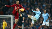 Gelandang Liverpool, Fabinho berebut bola dengan gelandang Manchester City, Bernardo Silva selama pertandingan lanjutan Liga Inggris di stadion Etihad (3/1). City menang tipis atas Liverpool 2-1. (AP Photo/Dave Thompson)