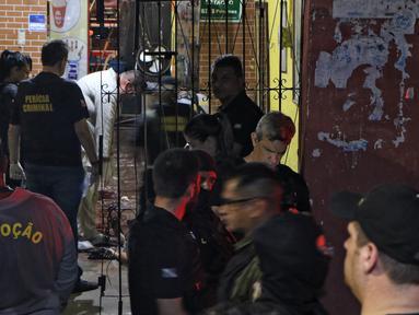 Sejumlah petugas saat mengevakuasi korban penembakan massal di sebuah bar di kota Belm, negara bagian utara Par, Brazil (19/5/2019). Sebanyak 11 orang dilaporkan tewas dalam serangan yang dilakukan 7 pria bersenjata tersebut. (Claudio Pinheiro/Agencia Panamazonica/AFP)