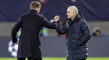 Pelatih Tottenham Hotspur, Jose Mourinho dan pelatih RB Leipzig Julian Nagelsmann menyentuh lengan mereka alih-alih berjabat tangan karena virus corona usai pertandingan leg kedua babak 16 besar Liga Champions di Red Bull Arena, Jerman (10/3/2020). (AP Photo/Michael Sohn)