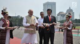 Presiden Joko Widodo (Jokowi) dan PM India Narendra Modi memotong pita saat meresmikan pameran Indonesia-India Kite  Exhibition di kawasan Monas, Jakarta, Rabu (30/5). Pada pameran tersebut, dipamerkan puluhan layang-layang. (Merdeka.com/Iqbal S. Nugroho)