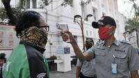 Petugas memeriksa suhu tubuh pengunjung kompleks wisata Kota Tua, Jakarta, Selasa (2/6/2020). Jelang berakhirnya PSBB di Jakarta, pengelola Kota Tua menyiapkan protokol kesehatan new normal bagi pengunjung. (merdeka.com/Iqbal S. Nugroho)