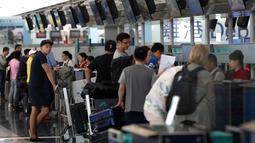Calon penumpang pesawat memeriksa penerbangan mereka di bandara Hong Kong, Rabu (14/8/2019). Bandara Hong Kong kembali membuka penerbangan keberangkatan pada Rabu pagi setelah sempat lumpuh selama dua hari akibat demonstran menduduki salah satu bandara tersibuk di dunia tersebut. (AP/Vincent Thian)