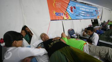 Dua anak mengintip proses pengambilan donor darah di Masjid Kauman,Yogyakarta, (11/6/2016).Safari donor darah ramadan pundi amal SCTV di sambut antusias oleh masyarakat.(Boy Harjanto)