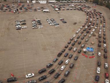Pemandangan udara saat orang-orang antre di dalam mobil di lokasi pengujian Covid-19 drive-thru di Stadion Dodger di Los Angeles, California, Rabu (18/11/2020). Pejabat kesehatan Los Angeles County memperingatkan adanya peningkatan tajam dalam jumlah kasus COVID-19 dan rawat inap. (Robyn Beck/AFP)