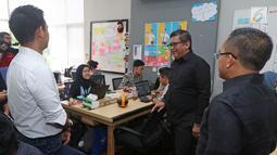 Sekjen PDIP Hasto Kristiyanto berbincang saaat melihat-lihat kantor ruangguru.com di Jakarta, Jumat (4/5). PDIP menunjuk Bupati Banyuwangi Abdullah Azwar Anas untuk memimpin proyek kerja sama dengan ruangguru.com. (Liputan6.com/Herman Zakharia)